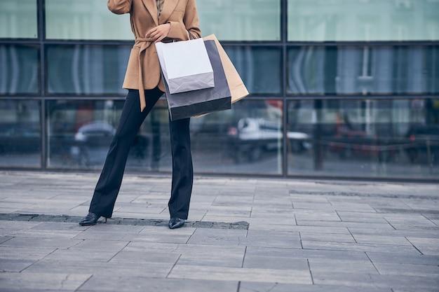 Close em uma senhora magra em roupas elegantes em pé na rua perto de um prédio de escritórios