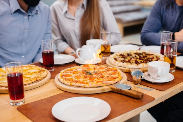 Close exclusivo de pizza quente pegando fogo durante um jantar amigável