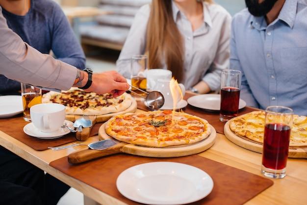 Close exclusivo de pizza quente pegando fogo durante um jantar amigável. Foto Premium