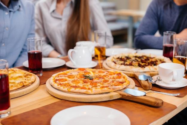 Close exclusivo de pizza quente pegando fogo durante um jantar amigável.