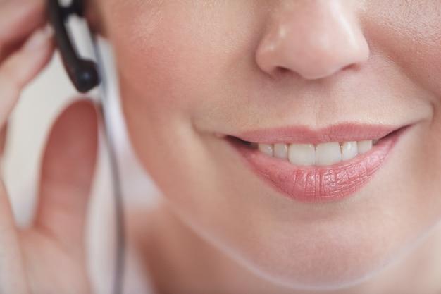 Close extremo de operador irreconhecível de call center usando fone de ouvido, foco no sorriso feminino agradável