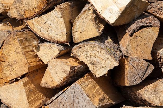 Close fotografado de um tronco amarelo de uma madeira serrada cortada em lenha. a madeira é empilhada paralelamente às linhas anteriores. foto da vida na aldeia