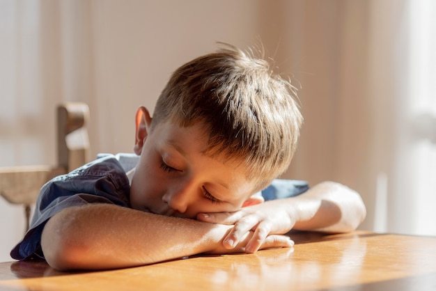 Close garoto dormindo na mesa