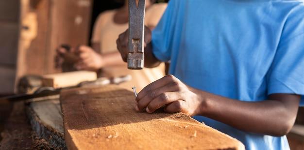 Close garoto trabalhando com madeira