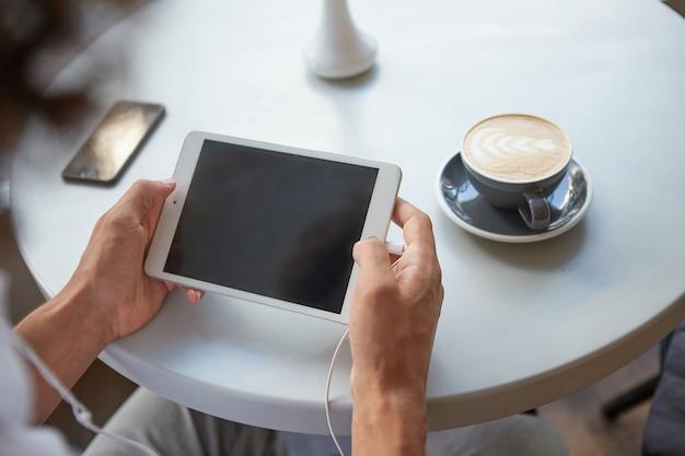 Close interno das mãos de um homem segurando um tablet com fones de ouvido conectados, fazendo uma pausa para o almoço com uma xícara de café, mantendo o smartphone na mesa