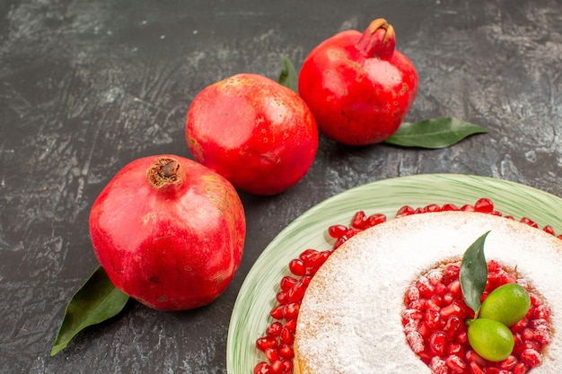Close lateral de um apetitoso bolo de romãs vermelhas com folhas um prato de um apetitoso bolo