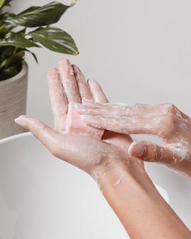 Close limpando profundamente as mãos com água e sabão