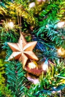 Close lindo de um enfeite de ouro em uma árvore de natal com luzes