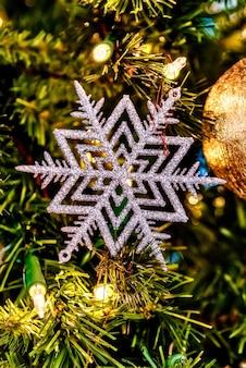 Close lindo de um floco de neve branco e outras decorações em uma árvore de natal com luzes