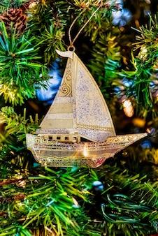 Close lindo de um veleiro dourado em uma árvore de natal com luzes