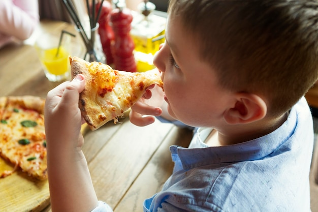 Close menino com uma fatia de pizza