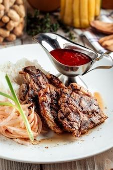 Close na carne grelhada com arroz e molho vermelho na mesa de madeira