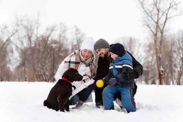 Close na família feliz brincando na neve com o cachorro