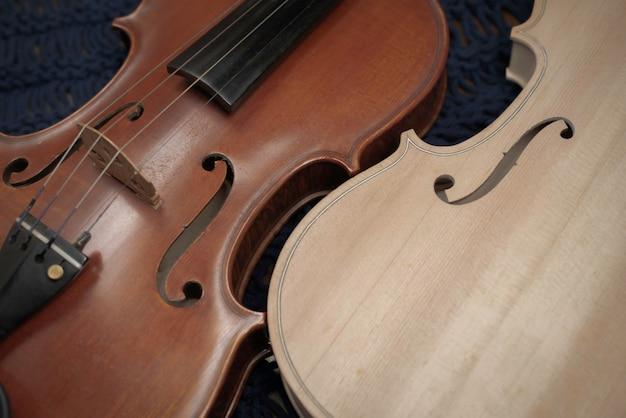 Close na frente do violino concluído colocando um violino bruto