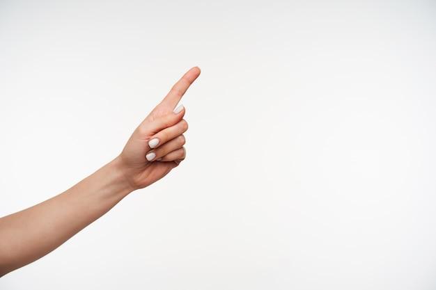 Close na mão de uma jovem mulher de pele clara, mantendo o dedo indicador levantado