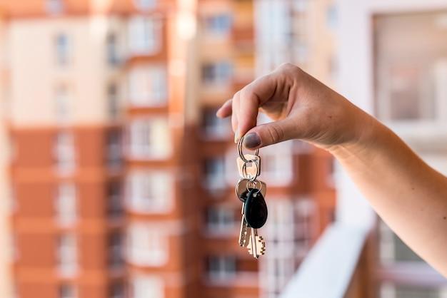 Close na mão feminina com as chaves do novo apartamento