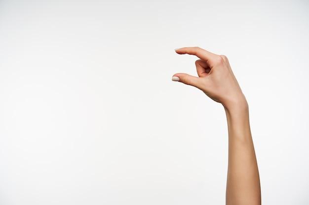 Close na mão levantada de uma jovem senhora de pele clara medindo itens invisíveis