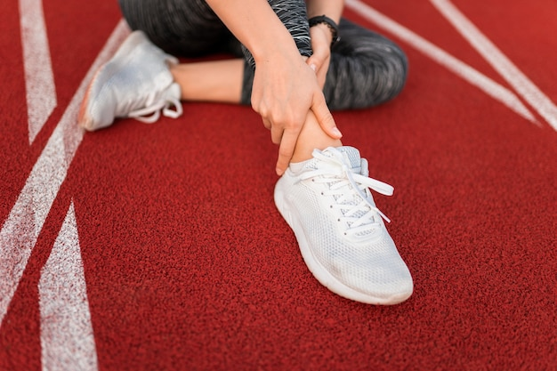 Close na mulher sentada na pista do estádio com uma perna machucada