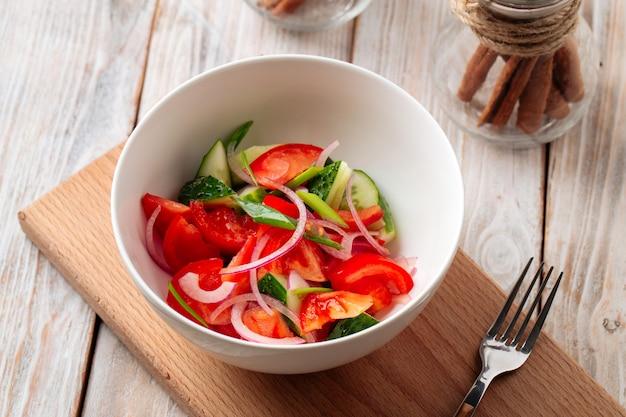 Close na salada de legumes frescos com pepinos e tomates em uma tigela branca