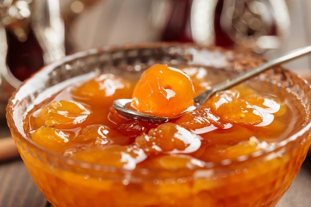 Close na tigela de vidro de geleia de cereja branca na mesa de madeira