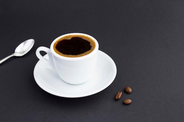 Close na xícara branca com café preto e grãos de café no fundo escuro