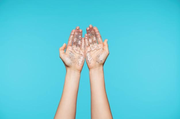 Close nas mãos atraentes mostrando as palmas para cima com todos os dedos juntos