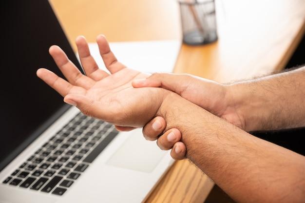 Close nas mãos de um trabalhador com síndrome de escritório