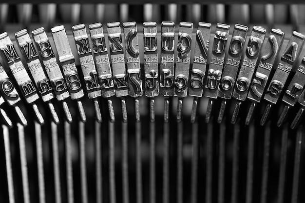 Close nas teclas pretas e escuras de uma máquina de escrever antiga