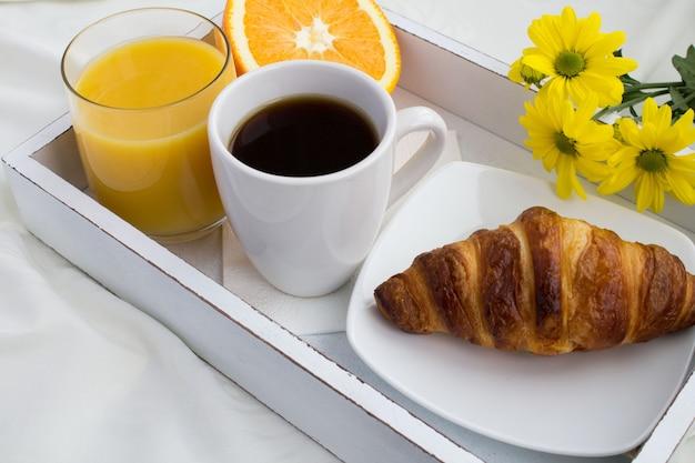 Close no café da manhã na bandeja de madeira branca