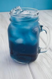 Close no chá azul gelado no copo na superfície branca