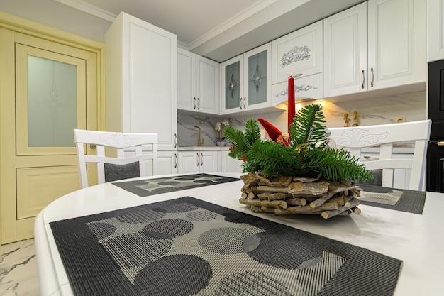 Close no interior branco aconchegante da cozinha clássica moderna com móveis e eletrodomésticos de madeira, decorado para o natal