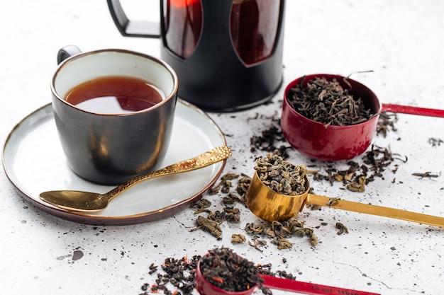 Close no jogo de chá com colheres e uma xícara no fundo branco