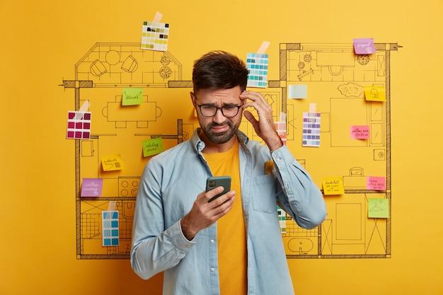 Close no jovem designer se preparando para renovar ao lado do esboço do plano mestre da casa