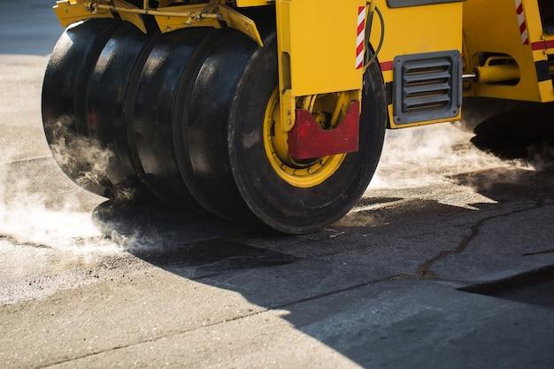 Close no rolo compactador compactando asfalto