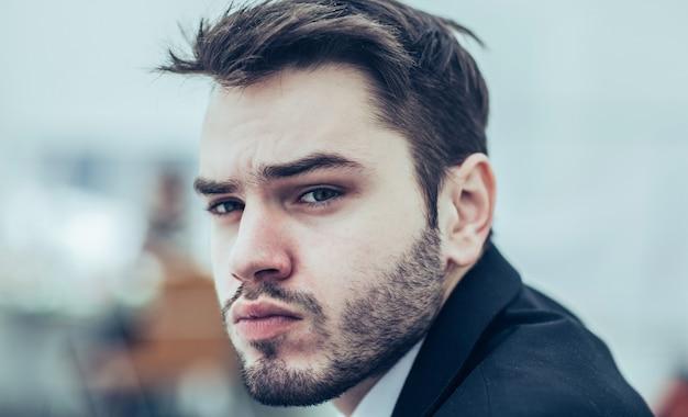 Close no rosto de um empresário sério no fundo do escritório