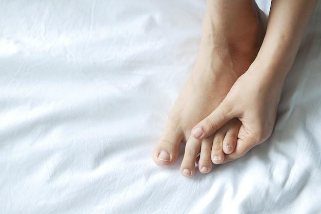 Close nos pés da mulher e massagem nas mãos no local da lesão