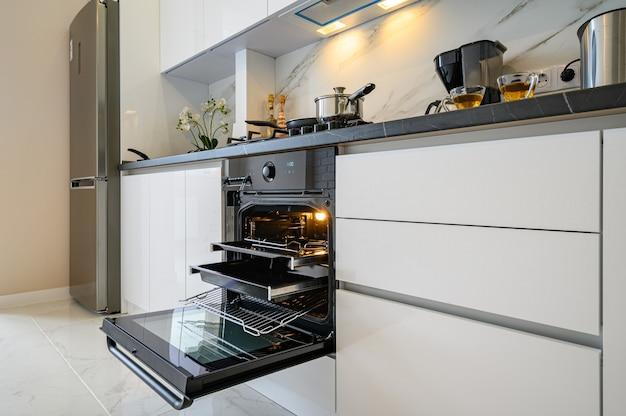 Close para abrir a porta do forno na cozinha clássica branca moderna