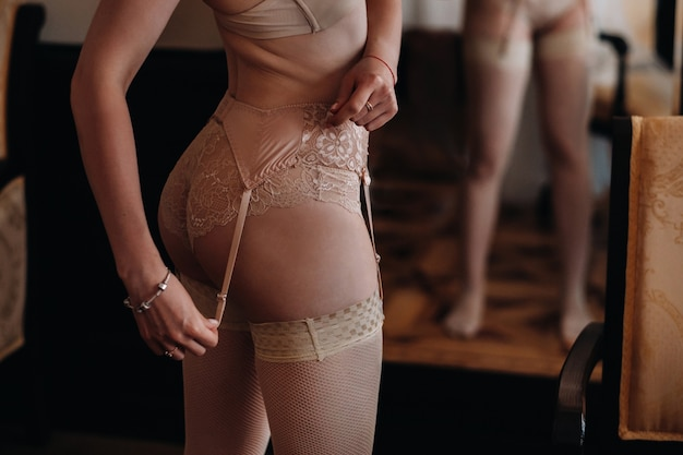 Close por trás de uma bela figura de uma garota vestindo roupas íntimas