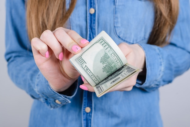 Close recortado de lindas mãos femininas com unhas compridas rosa brilhante manicure nos dedos segurando calculando dinheiro velho vestindo roupas jeans parede cinza isolada