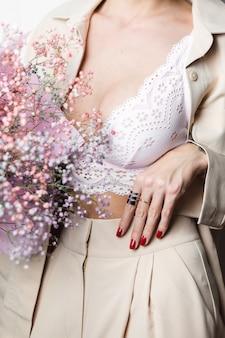 Close, tiro sem cabeça mulher de terno bege e sutiã branco segurando buquê de flores secas coloridas manicure vermelha dois anéis nos dedos