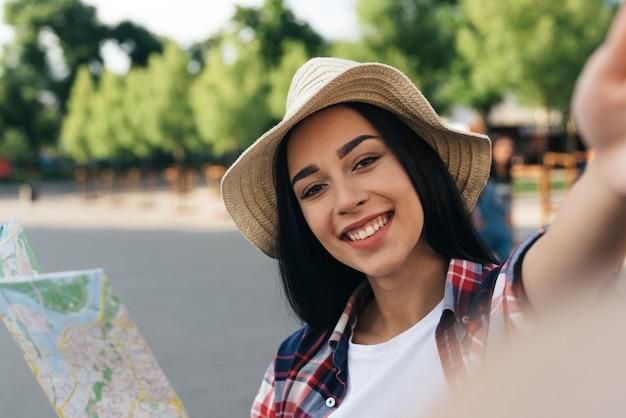 Close-u, de, mulher sorridente, segurando, mapa, e, levando, selfie, ao ar livre