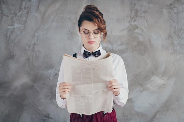 Close-uo retrato dela ela bonita atraente adorável muito mandona autoritária focada garota de cabelos ondulados financista lendo periódico financeiro isolado no fundo cinza da parede industrial de concreto