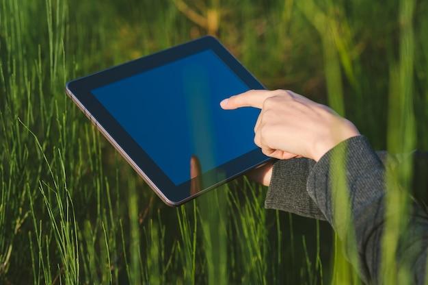 Close-up, a garota pressiona o dedo no tablet no fundo de uma bela natureza ao ar livre.