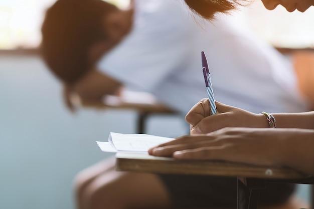 Close up à mão da pena de terra arrendada do estudante e tomada do exame na sala de aula com esforço para o teste da educação.