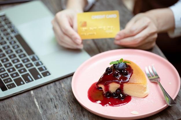 Close up, a mão de uma jovem empresária asiática é dona de uma cafeteria, segurando um cartão de crédito e colocando um bolo de frutas vermelhas na mesa para dizer aos clientes que paguem pelo serviço