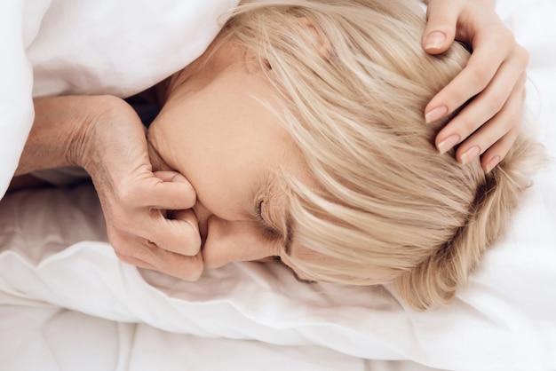 Close-up a menina está cuidando de uma mulher idosa na cama em casa