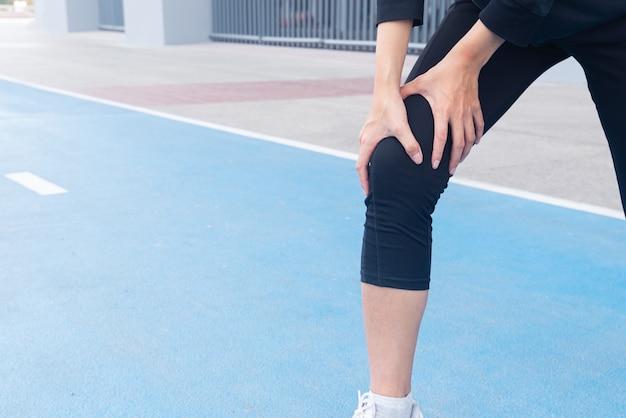Close-up acidente de lesão no joelho entre exercício corrida e corrida na pista de corrida.
