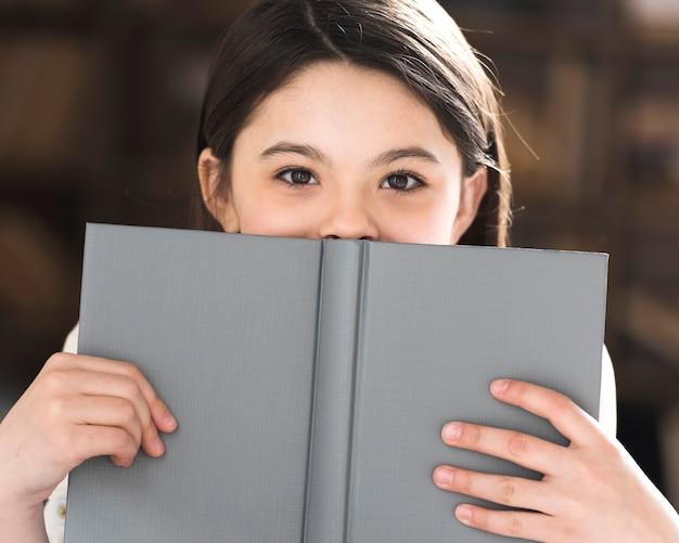 Close-up adorável menina segurando um livro