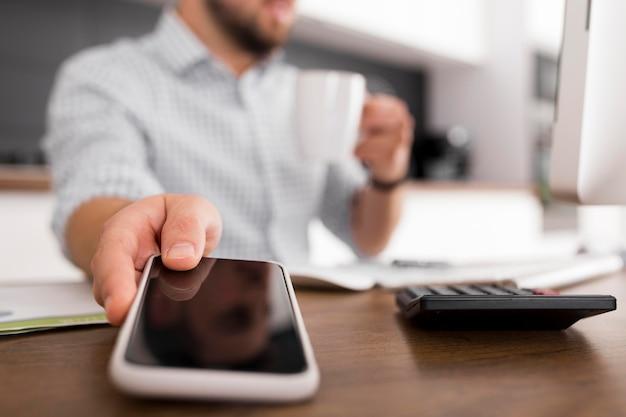Close-up adulto do sexo masculino segurando um telefone celular