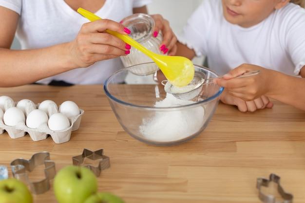 Close-up adulto e criança cozinhando juntos